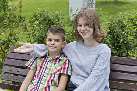 Brother and sister are sitting on bench in summer Stock Photo
