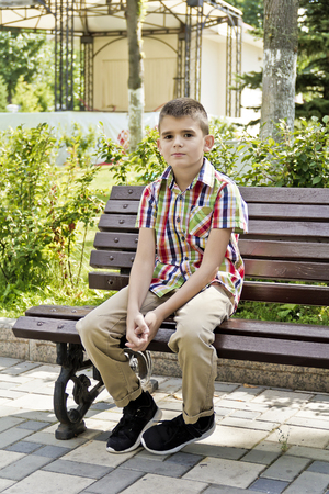 Cute brunette boy are sitting on the bench in summer