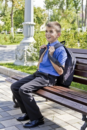 Brunette boy are sitting on the bench with school backpack Stock Photo
