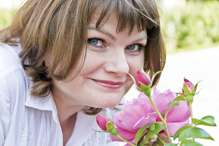 Beautiful smiling woman in white are sniffing peonies