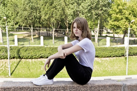 Girl fourteen years old in white are sitting on the curb