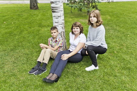 Happiest mother with daughter and son on green grass Stock Photo