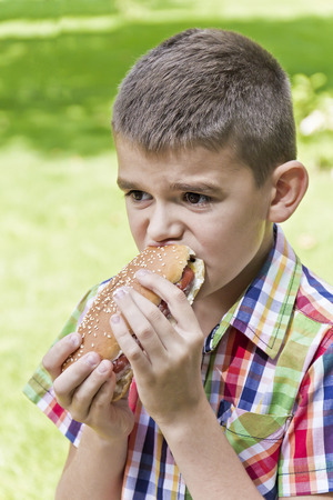 Cute boy are eating hotdog with appetite on green background Stock Photo