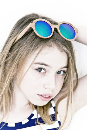 Blond girl eleven years old standing near white wall with green sunglasses