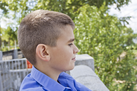 Profile of cute brunette boy eleven years old in summer background