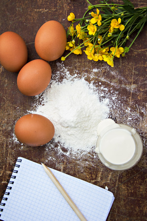 eggs, flour, sour cream, cottage cheese and notepads recipes are on the table photo