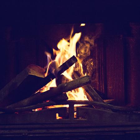 Holzverbrennung in einem gemütlichen Kamin zu Hause. Feuer brennt im Kamin. Winter- und Weihnachtsferienkonzept.