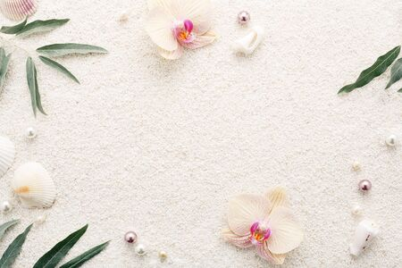 Summer frame of seashells, flowers & pearls on white beach sand. Pastel background, copy space, top view. Relaxation Spa concept.