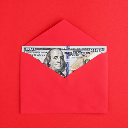 A hundred American dollars in cash in envelope on red background. Money, finance concept. Top view, minimal.