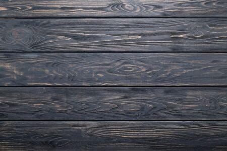 Dunkelgrauer Hintergrund des alten rustikalen Holztischs, Plankenbeschaffenheit, Holzwand.