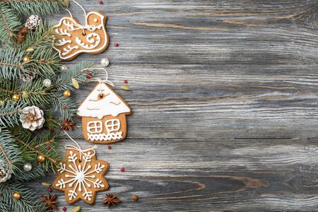 Frame of Gingerbread cookies and Christmas decorations on spruce over wooden background, copy space. Holiday greeting card.