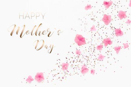 金色闪光的纸屑和白色背景上的粉色花朵。春天的假期。短信母亲节快乐卡片。