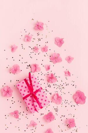 礼物盒花和闪烁在桃红色背景的五彩纸屑。春天,暑假。生日,母亲节。复制空间。平躺。