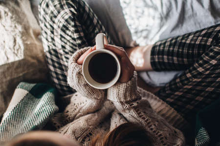 Cozy autumn or winter atmosphere. Young woman with cup of tea and warm sweater is seating at home near the window. Stock Photo
