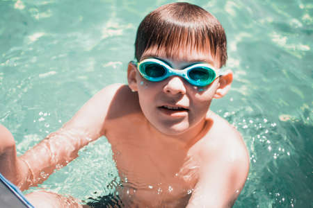 Boy in swimming glasses swims in the pool. Swimming in the pool. Summer activities.