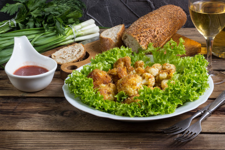 freshly prepared: Freshly prepared breaded cauliflower in bowl with tkemali to dip. Selective Focus.