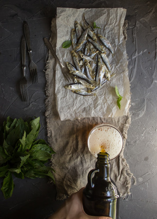 sprat: Dried fish on the brown paper. And beer in the botlle. Selective focus
