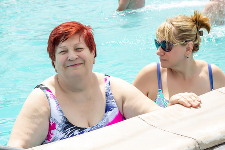 An elderly woman and her daughter. Swimming pool with a warm thermal spring. Kazinka south of Russia
