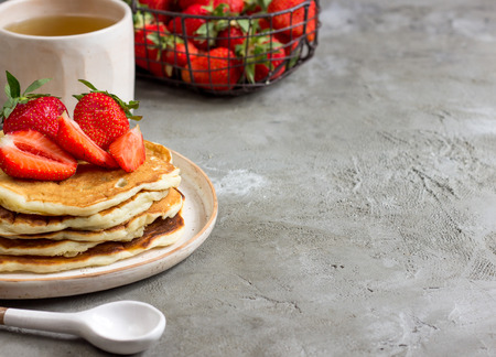 hotcakes: Pancakes with strawberries on a handmade ceramic plate. Selective focus. Space for text
