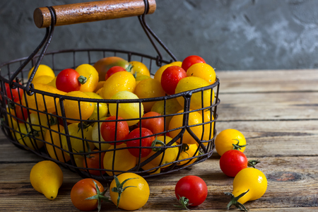 Colorful tomatoes in the basket, red tomatoes, yellow tomatoes. Tomatoes background. vintage wooden background