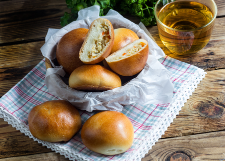 Russian pirozhki on wooden table. Baked patties stuffed with cabbage. Selective focus