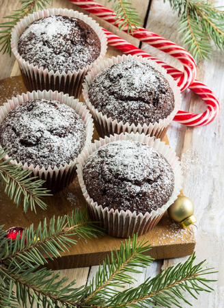 Christmas sweets and desserts, Chocolate cupcakes with powdered sugar, on wooden background with Christmas tree and balls, copy space Stock Photo