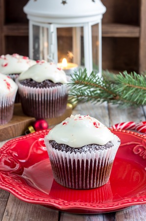 Christmas sweets and desserts, Chocolate cupcakes with candy cane crumbs, on wooden background with Christmas tree and balls, copy space