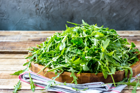 Fresh arugula leaves on wooden bowl, rucola. Arugula rucola on wooden old background. Arugula rucola for salad. Selective focus, blank space. Stock Photo
