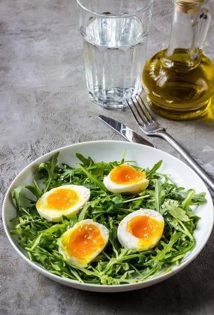 Spring salad with fresh vegetables: arugula, egg, and sesame on a gray grunge background. Selective focus