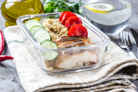 Healthy meal prep containers with quinoa, chicken and arugula Selective focus Stock Photo
