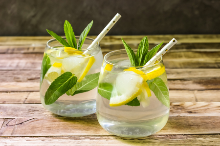 Detox water with lemon and mint. Summer drink in glass on rustic wooden background. Copy space