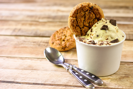 Ceramic bowl of banana ice cream dessert with chocolate and cookies, close-up on wooden background with copy space. Selective focus Stock Photo