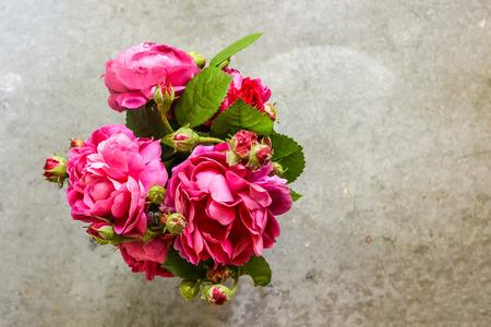 Ramo fresco de flores rosas rosadas, hoja verde en florero de vidrio sobre fondo gris. Concepto de horario de verano. Naturaleza muerta, estilo rústico. Decoración floral fresca, para el hogar.