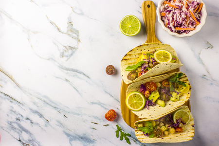 Healthy corn tortillas with chickpeas, tomatoes, avocado, fresh arugula, limes over light grey marble table background, top view. Healthy food, gluten-free, allergy-friendly, weight loss concept