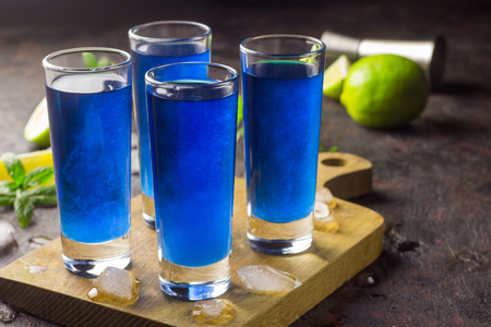 Blue curacao liqueur with lime and mint on the wooden serving board, selective focus