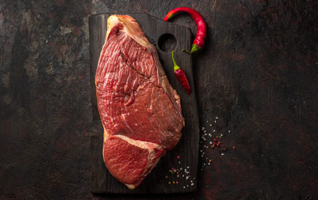 Raw entrecote steak on a dark wooden board, copy space, top view