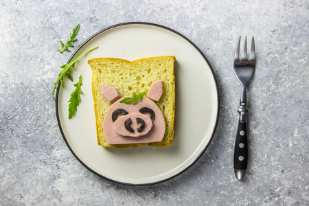 Funny animal sandwich for kids shaped cute pig with boiled sausage and olives on white plate on grey
