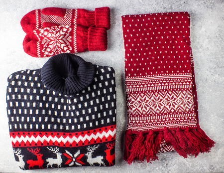 Christmas sweater, scarf and mittens with pattern on concrete