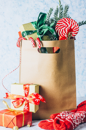Paper shopping bag full of gift boxes Christmas ornamented with red ribbon against an off-white