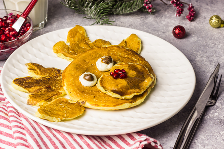 Funny Christmas breakfast of pancakes in the form of a deer. Top view