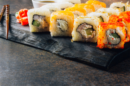 Japanese cuisine california roll and tuna roll on black wooden board served with wasabi and soy sauce 写真素材