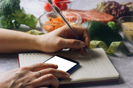 Donna che utilizza l'applicazione contacalorie sul suo smartphone