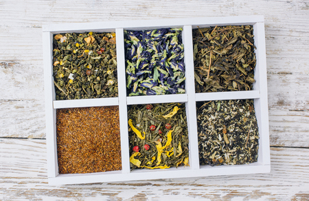 Assortment of dry tea in white wooden box. Tea types backgound: green, black, roybosh, anchan. Top view