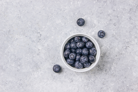 Top view of blue yogurt smoothie bowl made with blueberry, coconut flour on light concrete