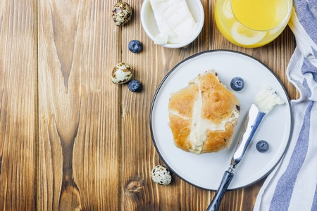 Traditional Easter treats cross buns, served with fresh butter and blueberries on wooden Stockfoto