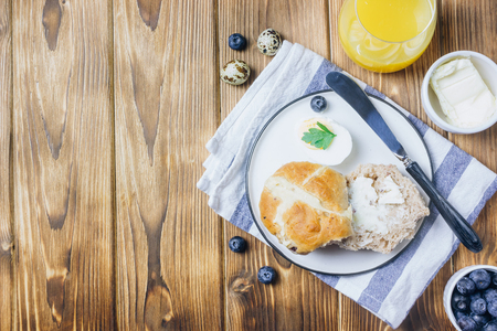 Traditional Easter treats cross buns, served with fresh butter and blueberries on wooden Stock Photo