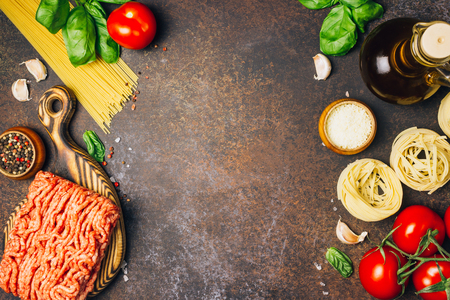 Bolognese pasta cooking concept: raw minced meat, tomatoes, pasta, parmesan, garlic, basil, olive oil on a dark background, Top view. place for text Archivio Fotografico