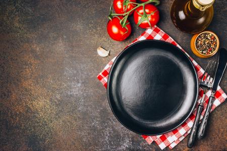 Italienisches Küchenkonzept, Handtuch, leerer schwarzer Teller, Besteck und Zutaten, Draufsicht