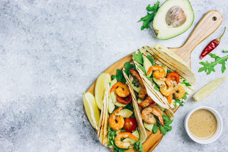 Seafood. Mexican food. Tortilla tacos with arugula, lemon, avocado and grilled shrimp pawns. On a light gray background. Top view copy space