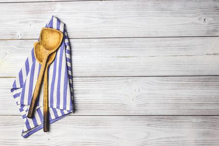 Cooking wooden utensils, olive oil, spices and light blue, white napkin on white wooden